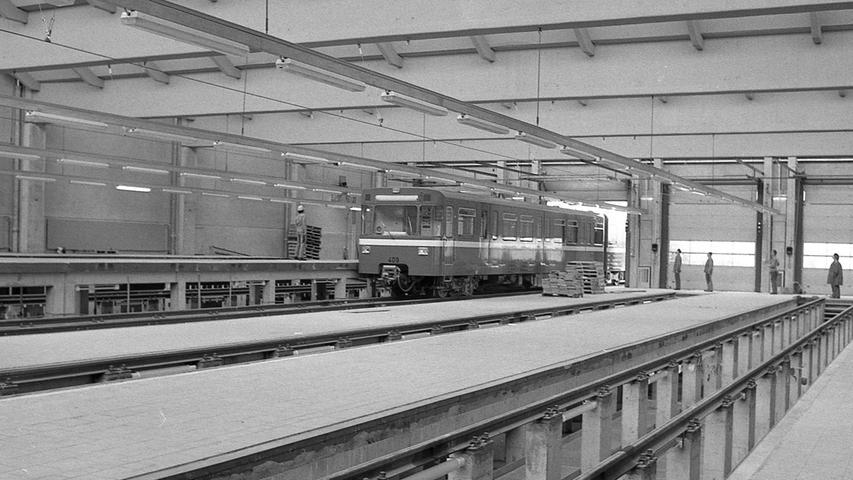 """Die Wagenwerkstatt mit vier Gleisen und tiefer gelegten Arbeitsbühnen: ein """"Pegnitz-Pfeil"""" wird gerade in die Halle geschoben.Hier geht es zum Kalenderblatt vom 19. März 1971:Geräuschlos über die Schienen"""