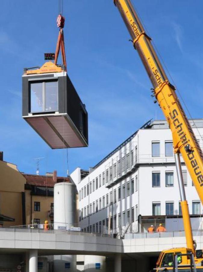 Ein Kran hob die Container auf ihren Platz am Klinikum rechts der Isar. Die enge Zufahrt wurde dabei frei gehalten.