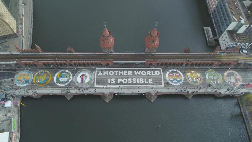 HANDOUT - 19.03.2021, Berlin: Aktivisten von Fridays for Future haben den Schriftzug «ANOTHER WORLD IS POSSIBLE