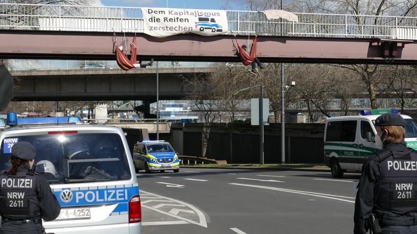 19.03.2021, Nordrhein-Westfalen, Köln: Polizisten stehen an einer Fußgängerbrücke auf der Südseite des Rheinufertunnels, von der sich zwei Aktivisten abgeseilt und so den darunterfahrenden Fahrzeugverkehr blockiert haben. Klimaaktivisten von Fridays for Future sind in mehreren Städten Nordrhein-Westfalens auf die Straße gegangen. Foto: Marius Fuhrmann/dpa +++ dpa-Bildfunk +++