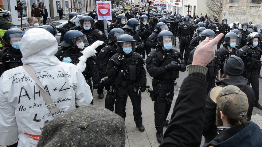 20.03.2021, Hessen, Kassel: Einsatzkräfte stehen bei einer Kundgebung unter dem Motto «Freie Bürger Kassel - Grundrechte und Demokratie» zwischen Teilnehmern. Eine Demonstration gegen die Corona-Maßnahmen ist unter Auflagen erlaubt worden. Foto: Swen Pförtner/dpa +++ dpa-Bildfunk +++