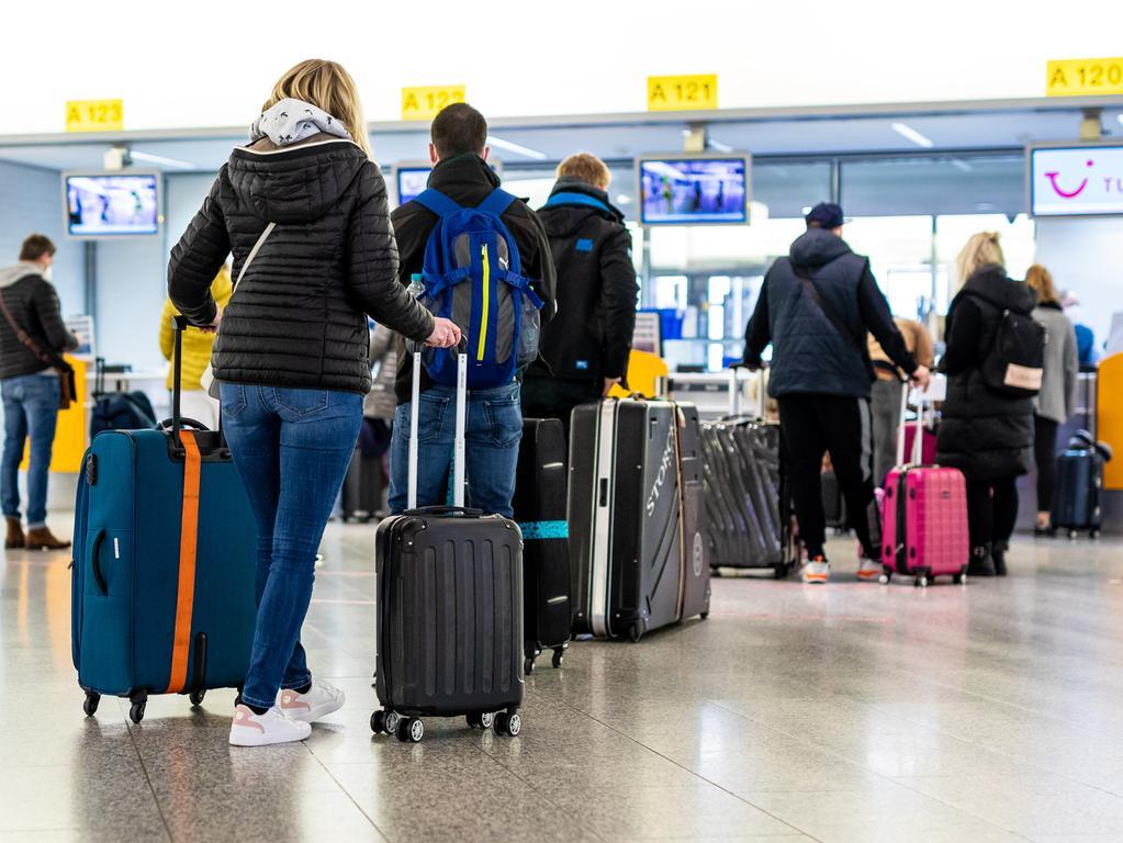 21.03.2021, Niedersachsen, Langenhagen: Fluggäste mit dem Reiseziel Mallorca stehen im Flughafen Hannover-Langenhagen am Check-in. Von Hannover aus fliegt der größte Reisekonzern Tui ab Sonntag nach langer Zwangspause wieder die ersten Urlauber nach Mallorca. Das Auslaufen der Reisewarnung für die Balearen macht dies möglich. Foto: Moritz Frankenberg/dpa +++ dpa-Bildfunk +++