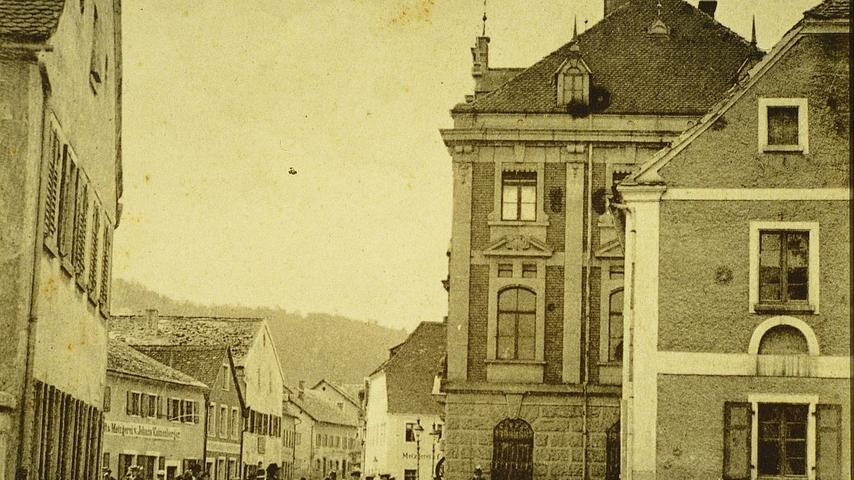 Das Treuchtlinger Rathaus (rechts) zu Beginn des 20. Jahrhunderts. Gut zu sehen sind links im Bild die einstigen Jurahäuser, die auf dem Areal des heutigen Rathausplatzes stehen.