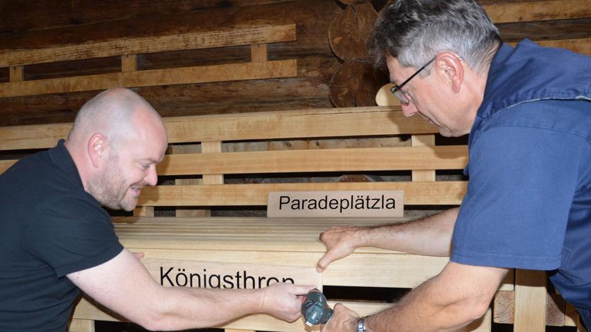 Betriebsleiter Christian Lenkl und Bauhof-Kollege Ewald Hack (rechts) montieren die Platzschilder in der Event-Sauna.