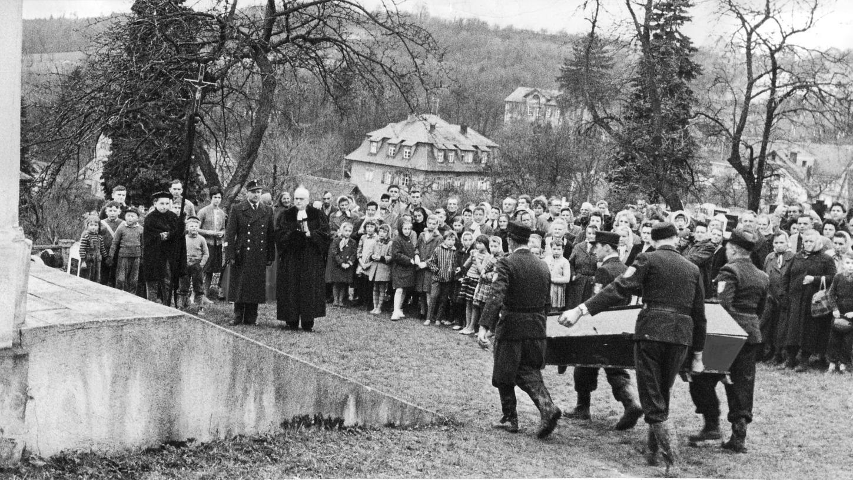 Männer, Frauen und Kinder aus Gräfenberg bilden auf dem Bergfriedhof der Stadt in der Fränkischen Schweiz ein stillschweigendes Spalier für die Opfer der Flugzeug-Katastrophe. Männer der Weißenoher Feuerwehr tragen die Särge in die Aussegnungshalle.
