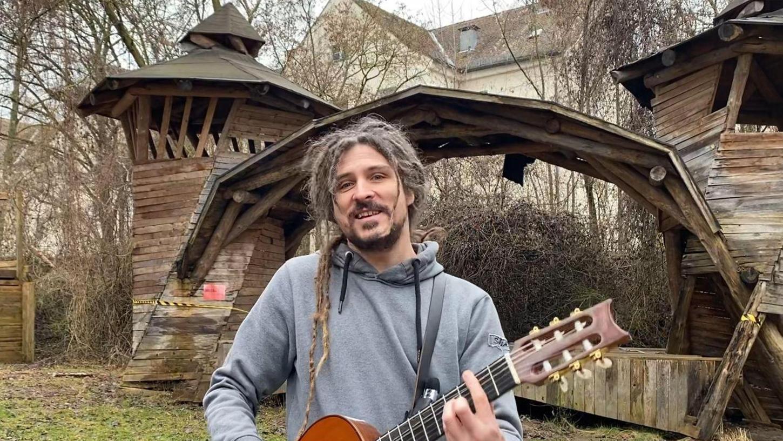 Liedermacher El Mago Masin vor der sanierungsbedürftigen Bühne am Aktivspielplatz Grünewaldstraße, für die bis zum 31. März noch viele Spenden gesammelt werden müssen.