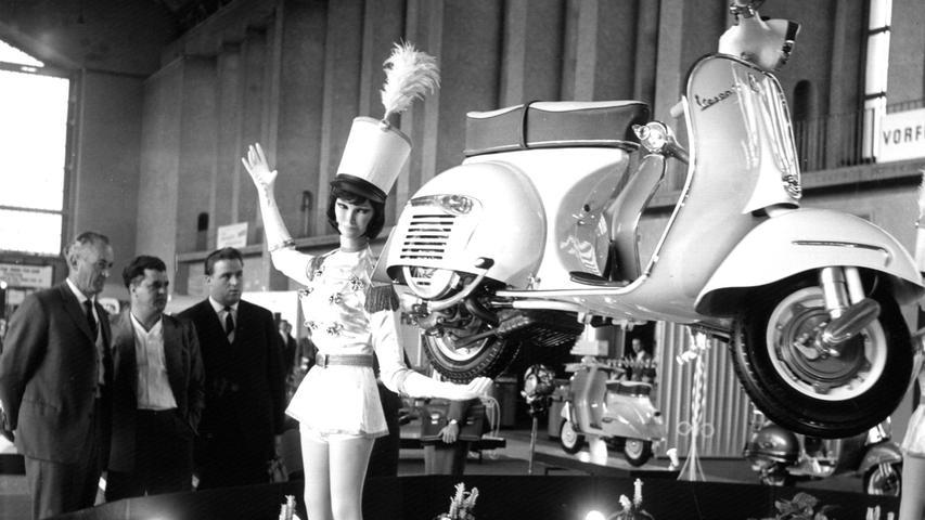 Eine Puppe trägt scheinbar mühelos mit einer Hand das neue Vespa-Modell auf der 5. Internationalen Fahrrad- und Motorradausstellung (IFMA) im September 1962 in Frankfurt am Main. Die erste Vespa kam vor 1946Jahren in Italien auf den Markt.