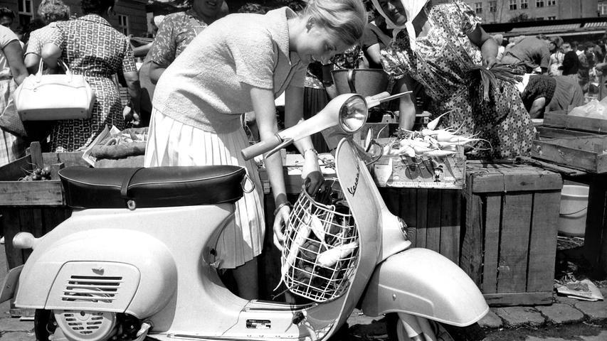 Eine Frau verstaut ihre Einkäufe in einem an ihrer Vespa angebrachten Korb, aufgenommen 1964. Die erste Vespa kam 1946in Italien auf den Markt.