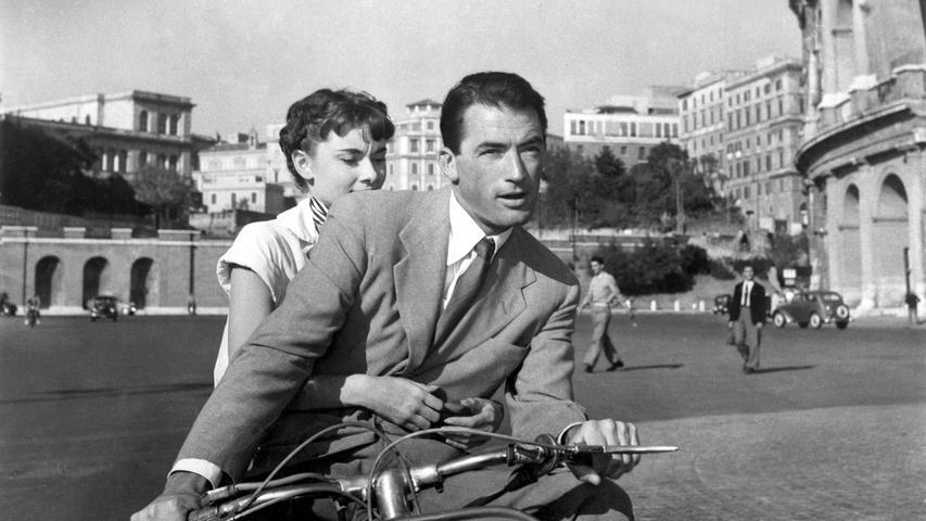Audrey Hepburn undGregory Peck1953 auf einer Vespa, die im Kinofilm Ein Herz und eine Kroneeine wichtige Rolle spielt.