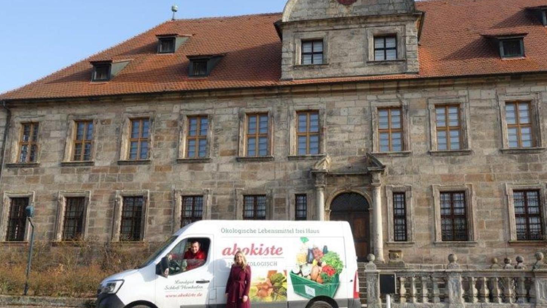Fertig für die Tour Richtung Eggolsheim und Pödeldorf: Sidney Roberts am Steuer eines Lieferfahrzeugs der Abokiste vor dem barocken Schlossgebäude des Landguts. Neben ihm Hannah Winkler von Mohrenfels, kurz mal ohne Maske fürs Bild.
