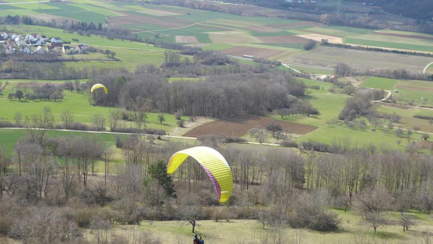 Zwei Paraglider peilen vom Walberla aus ihren Landeplatz an - in der noch recht kargen Landschaft.