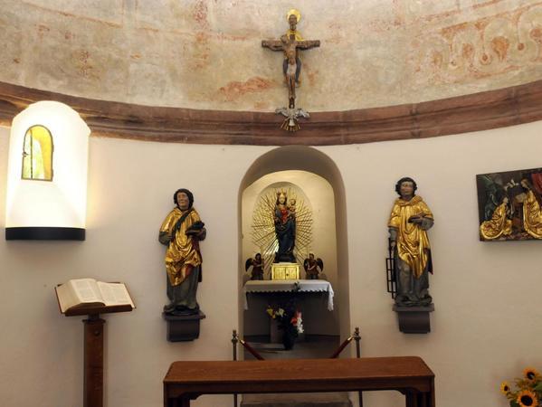 Ein Blick ins Innere der Rundkapelle: Im Zentrum steht eine Strahlenkranzmadonna mit dem Jesuskind am Arm, darüber hängt ein Kruzifix mit dem gekreuzigten Jesus.