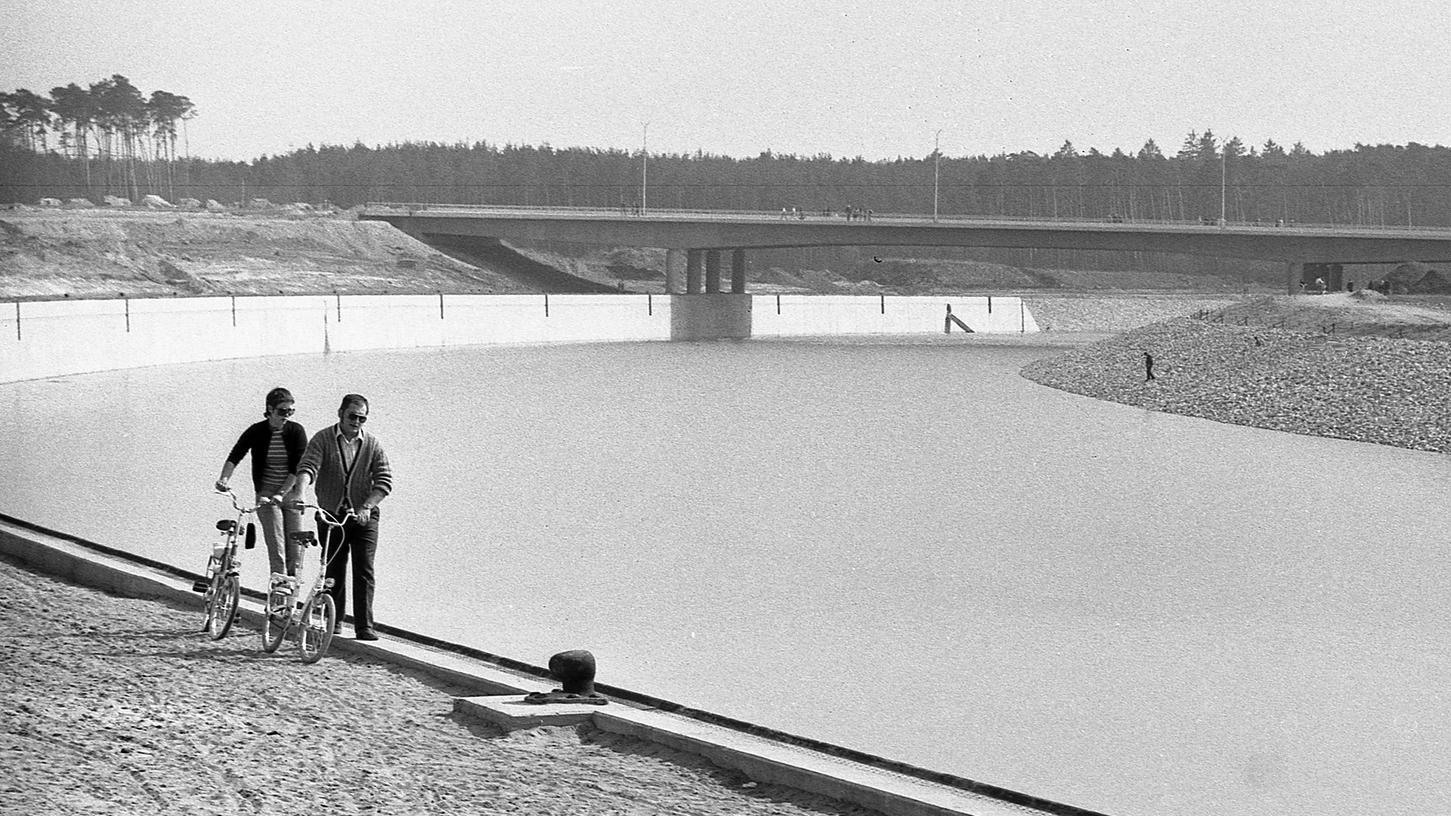 Eine Attraktion für viele Schaulustige vor allem an den Wochenenden: das erste Hafenwasser in Nürnberg. Jede Woche klettert der Wasserspiegel jetzt um sieben Zentimeter an den Kaimauern der Becken und der zweieinhalb Kilometer langen Kanalstrecke empor. Im Hintergrund streckt sich wuchtig und massiv die neue Brücke, die Maiach mit der Gartenstadt verbindet.
