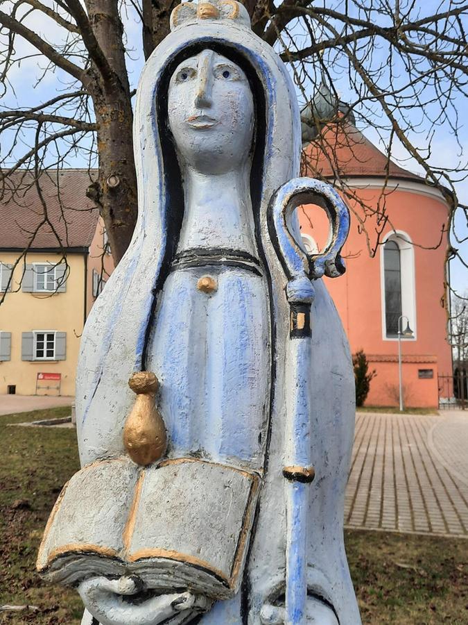 Vor der Kirche St. Michael in Gnotzheim werden die Jakobspilger von der Figur der Heiligen Walburga, ein Werk Ernst Steinackers, erwartet.