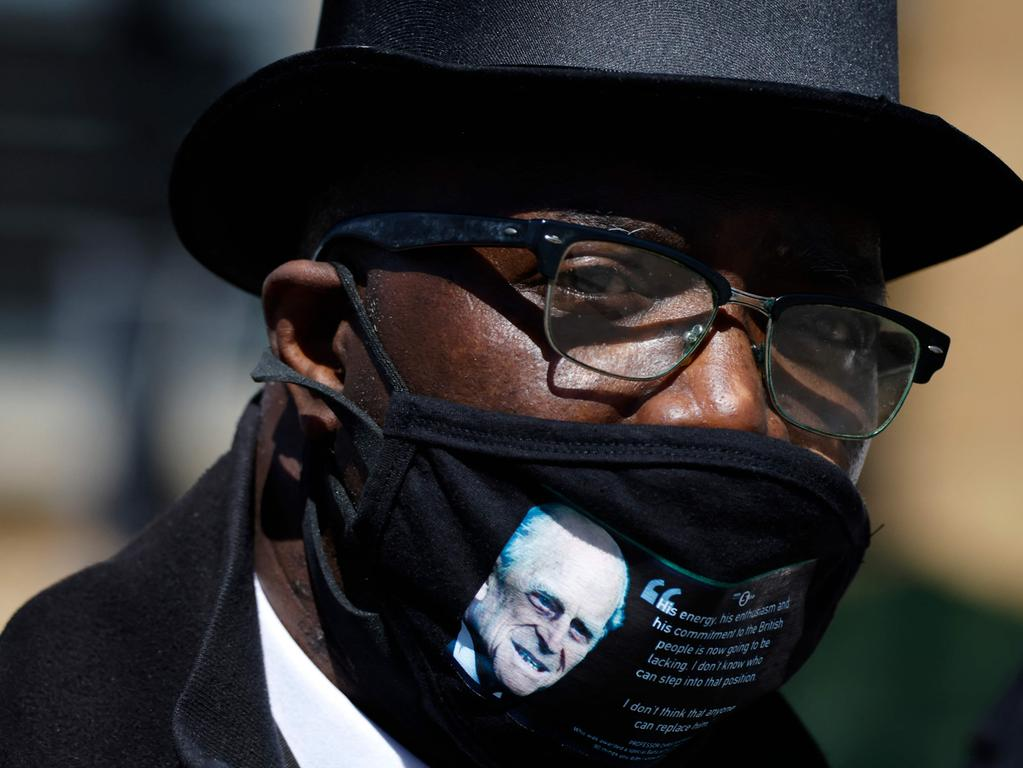 A man wearing a face covering bearing an image of Britain's Prince Philip, Duke of Edinburgh pays his respects outside Windsor Castle in Windsor, west of London, on April 17, 2021 ahead of the funeral of Britain's Prince Philip, Duke of Edinburgh. - Philip, who was married to Queen Elizabeth II for 73 years, died on April 9 aged 99 just weeks after a month-long stay in hospital for treatment to a heart condition and an infection. (Photo by Tolga Akmen / AFP)