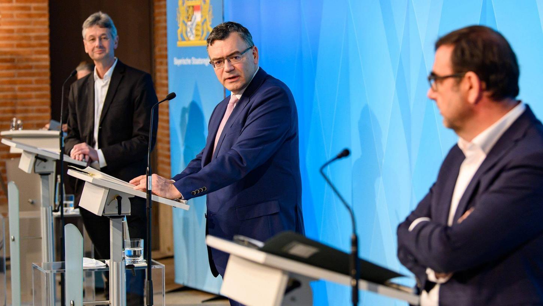 Kultusminister Piazolo, Gesundheitsminister Holetschek und Staatskanzleichef Hermann treten vor die Presse.