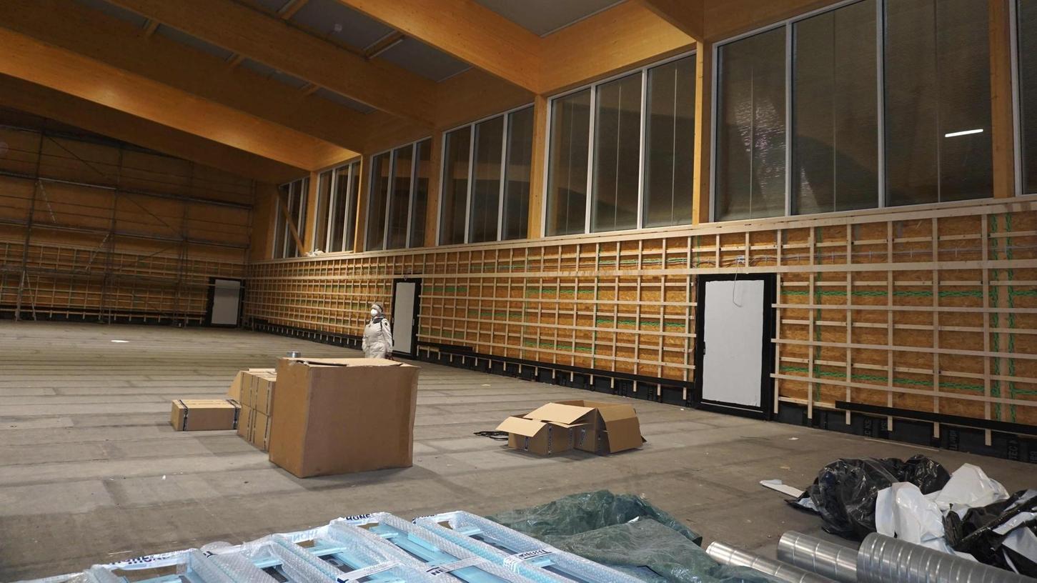 Der Gemeinderat Weisendorf ließ sich vor der Ratssitzung die Baustelle der neuen Ballsporthalle neben der Mehrzweckhalle zeigen. Um die Gestaltung des Hallenbodens wurde gestritten.