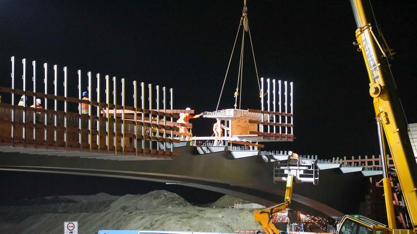 Torsten Hanspach (tha):.Erneut waren die Bauspezialisten der Firmen Eiffage und Johann Bunte im nächtlichen Einsatz auf der Autobahn A3. Diesmal galt es, große Betonfertigteile auf der neuen Autobahnbrücke zwischen Buchfeld und Elsendorf mit Betonfertigteilen zu befestigen. Die Stahlbrücke war im letzten Jahr vormontiert und im Ganzen herangefahren und eingesetzt worden (wir berichteten)..Obgleich weniger spektakulär, musste auch in dieser Nacht die Autobahn in beide Richtungen gesperrt werden. Die jetzt verbauten Betonteile sind die Grundlage für die spätere Fahrbahn. Am Haken des Autokrans herabschwebend, werden sie von den Arbeitern mit der Bücke verschweisst. Später wird auf die Armierung noch betoniert und die Fahrbahndecke aufgebracht, so dass dann die geplante Wiedereröffnung für den Verkehr sichtbar näher rückt..Bereits am kommenden Wochenende gehen die Arbeiten für den sechsstreifigen Ausbau der A3 weiter. Dann wird nahe des Erlanger Ortsteils Kosbach wieder eine Stahlbrücke eingesetzt, die die später abzubrechende alte Betonbrücke ersetzen wird...Torsten Hanspach (tha)