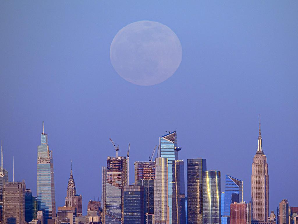The full moon of April, called the Super Pink Moon, rises over the skyline of Manhattan, New York on April 26, 2021. (Photo by Angela Weiss / AFP)