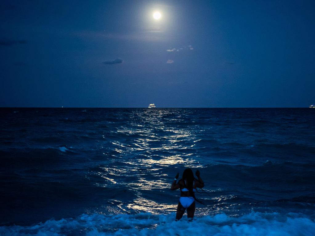 A woman stands in the water under the glow of the Super Pink Full Moon reflected in the ocean in Miami Beach, on April 26, 2021. (Photo by CHANDAN KHANNA / AFP)