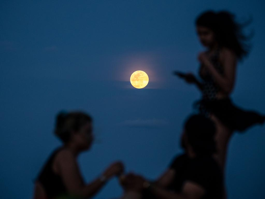 A full Pink Super moon lights up the sky as people relax on the beach in Miami Beach on April 26, 2021. (Photo by CHANDAN KHANNA / AFP)