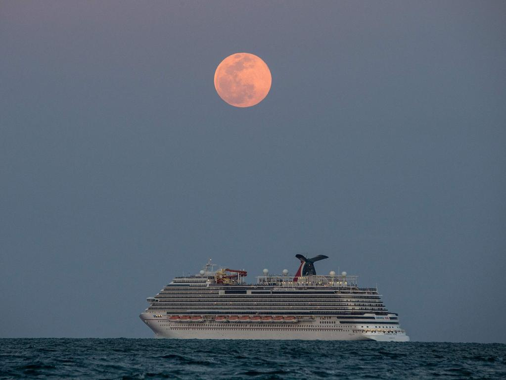 The Carnival Vista cruise ship is seen sailing during a full Pink Super moon in Miami Beach, on April 26, 2021. (Photo by CHANDAN KHANNA / AFP)