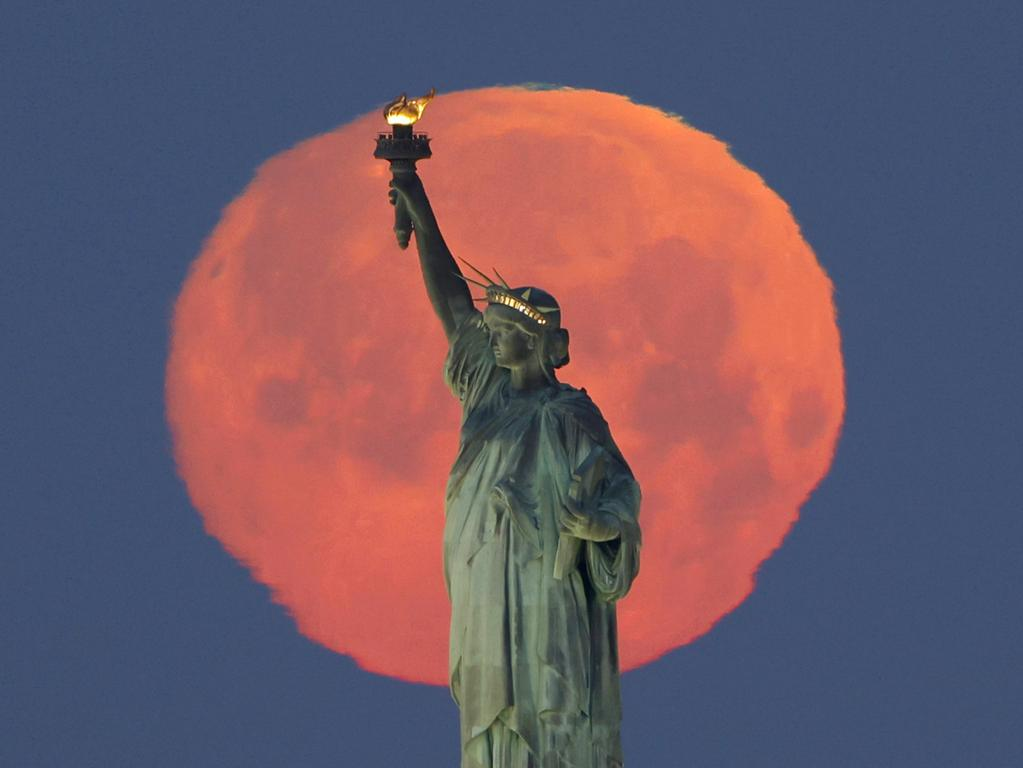 A Pink Supermoon sets behind the Statue of Liberty in New York City on Monday, April 26, 2021. This week s supermoon is dubbed the pink moon because of its timing close to flower blooming season. PUBLICATIONxINxGERxSUIxAUTxHUNxONLY NYP20210426104 JohnxAngelillo