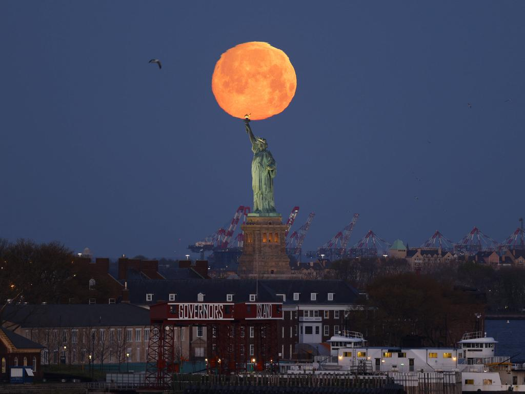 A Pink Supermoon sets behind the Statue of Liberty in New York City on Monday, April 26, 2021. This week s supermoon is dubbed the pink moon because of its timing close to flower blooming season. PUBLICATIONxINxGERxSUIxAUTxHUNxONLY NYP20210426101 JohnxAngelillo