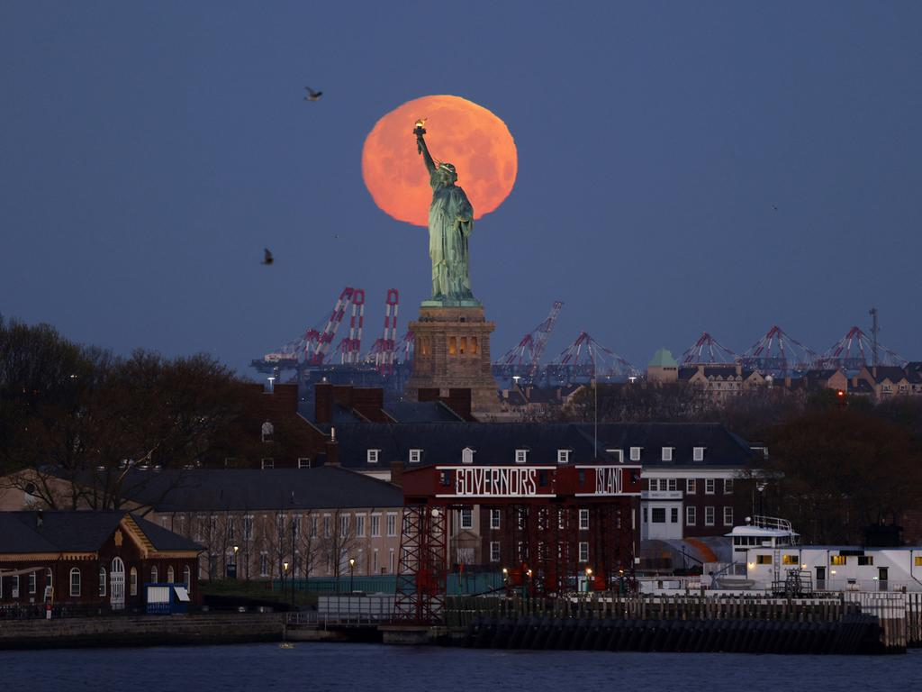 A Pink Supermoon sets behind the Statue of Liberty in New York City on Monday, April 26, 2021. This week s supermoon is dubbed the pink moon because of its timing close to flower blooming season. PUBLICATIONxINxGERxSUIxAUTxHUNxONLY NYP20210426102 JohnxAngelillo