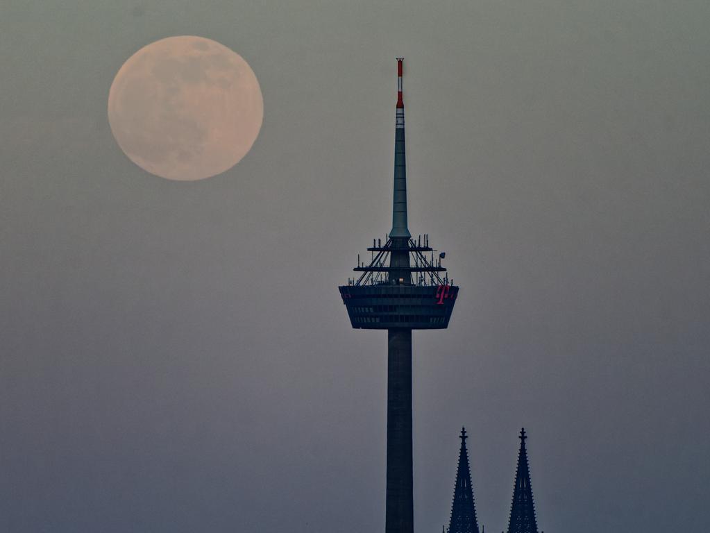 26.04.2021, Nordrhein-Westfalen, Köln: Der Mond steht kurz nach dem Aufgang über dem Fernsehturm