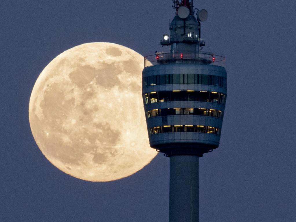 26.04.2021, Baden-Württemberg, Stuttgart: Der Vollmond geht hinter dem Stuttgarter Fernsehturm auf. Am 27. April 2021 kommt es zu einem sogenannten