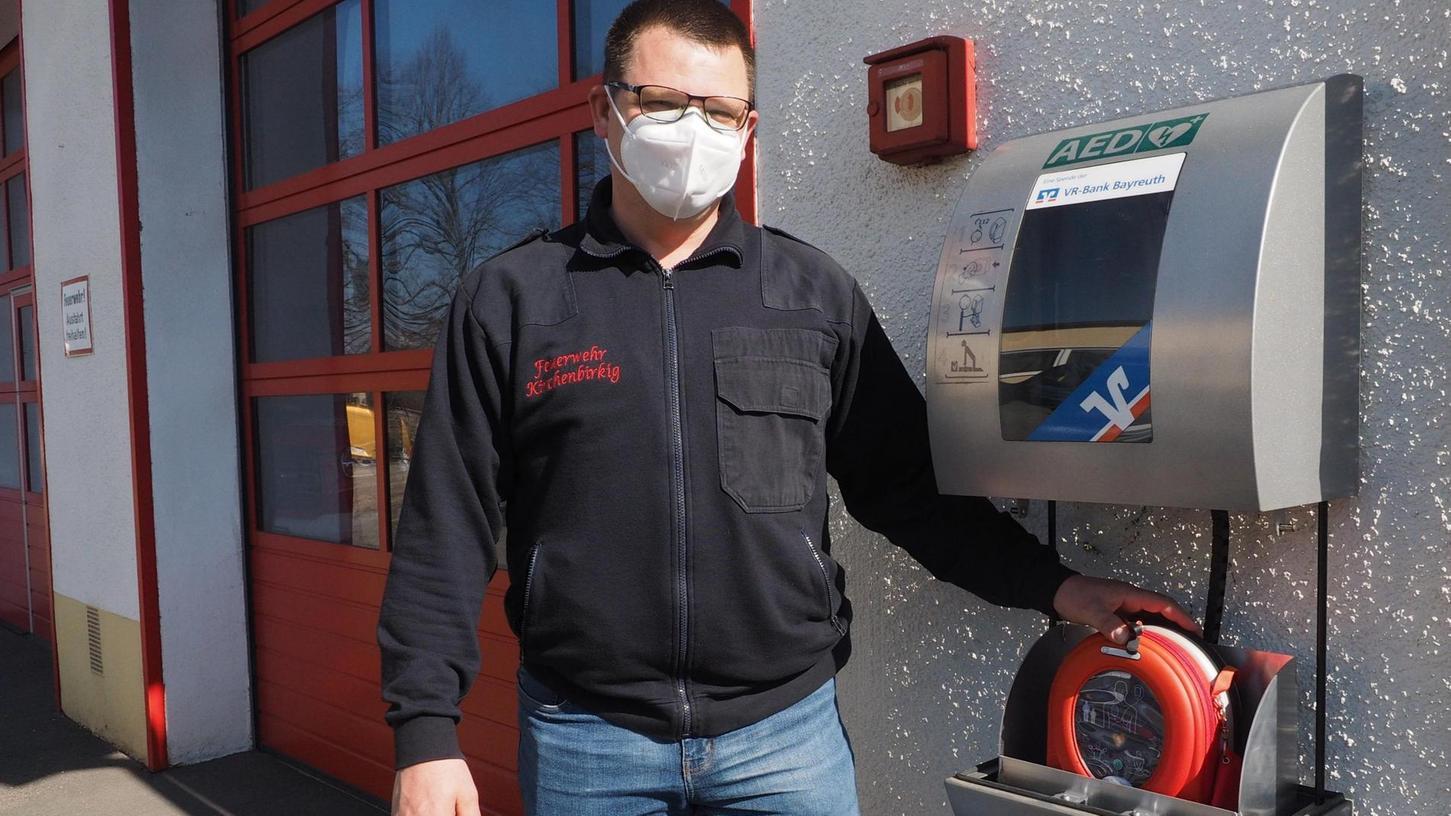 Clemens Herlitz ist Kommandant der Feuerwehr Kirchenbirkig und zeigt den Standort des Defibrillators am Gerätehaus. Er weiß, dass bereits nach einmaligem Einsatz teure Ersatzteile nötig sind.
