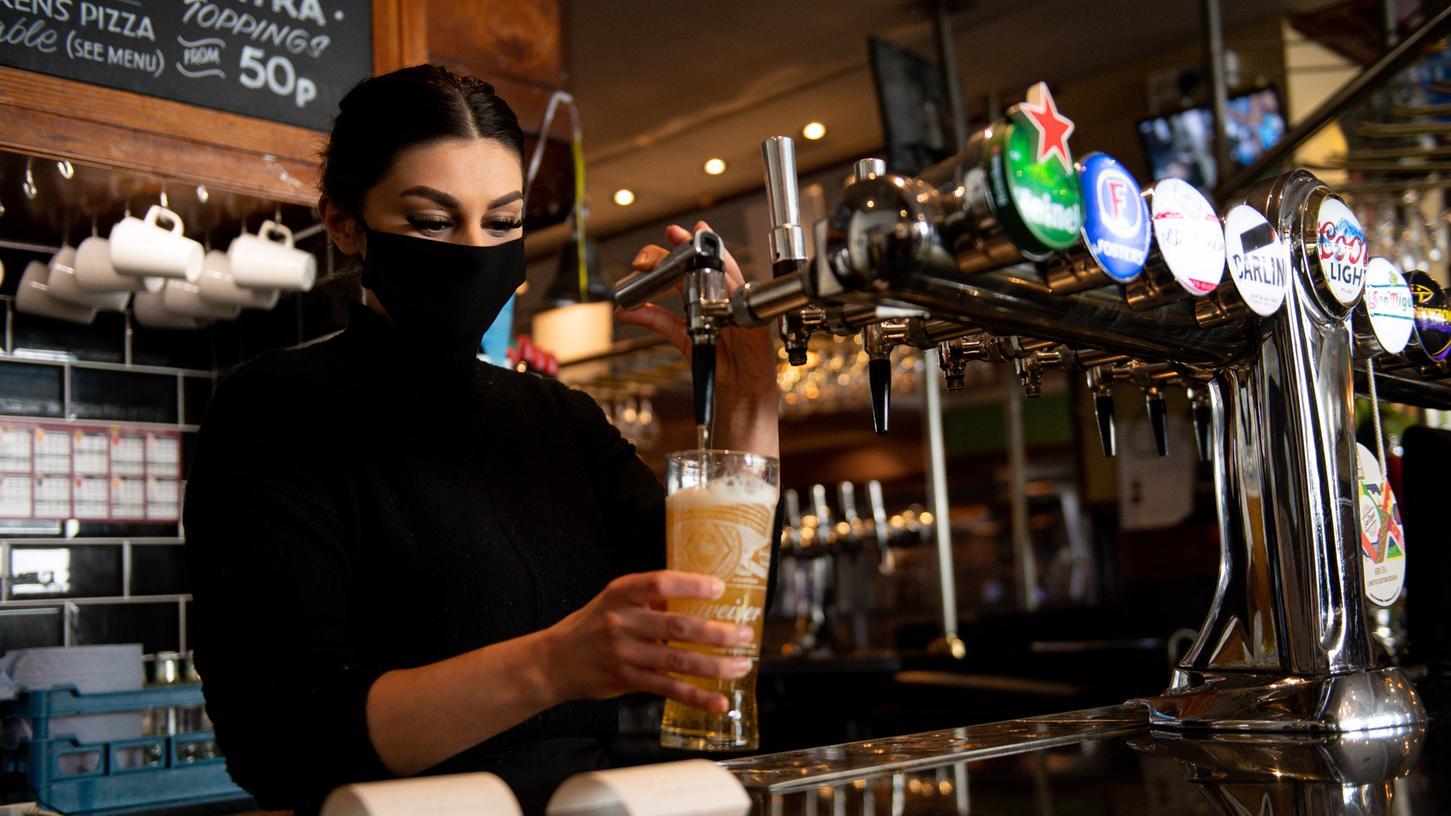 ARCHIV - 12.04.2021, Großbritannien, Birmingham: Eine Kellnerin im Pub «Figure of Eight» zapft ein Bier. Im größten Landesteil Großbritanniens wurden die Maßnahmen zur Eindämmung der Coronavirus-Pandemie weiter gelockert. Nach dem unerwartet großen Durst der ersten Gäste wird in britischen Pubs nun langsam das Bier knapp. Foto: Jacob King/PA Wire/dpa +++ dpa-Bildfunk +++