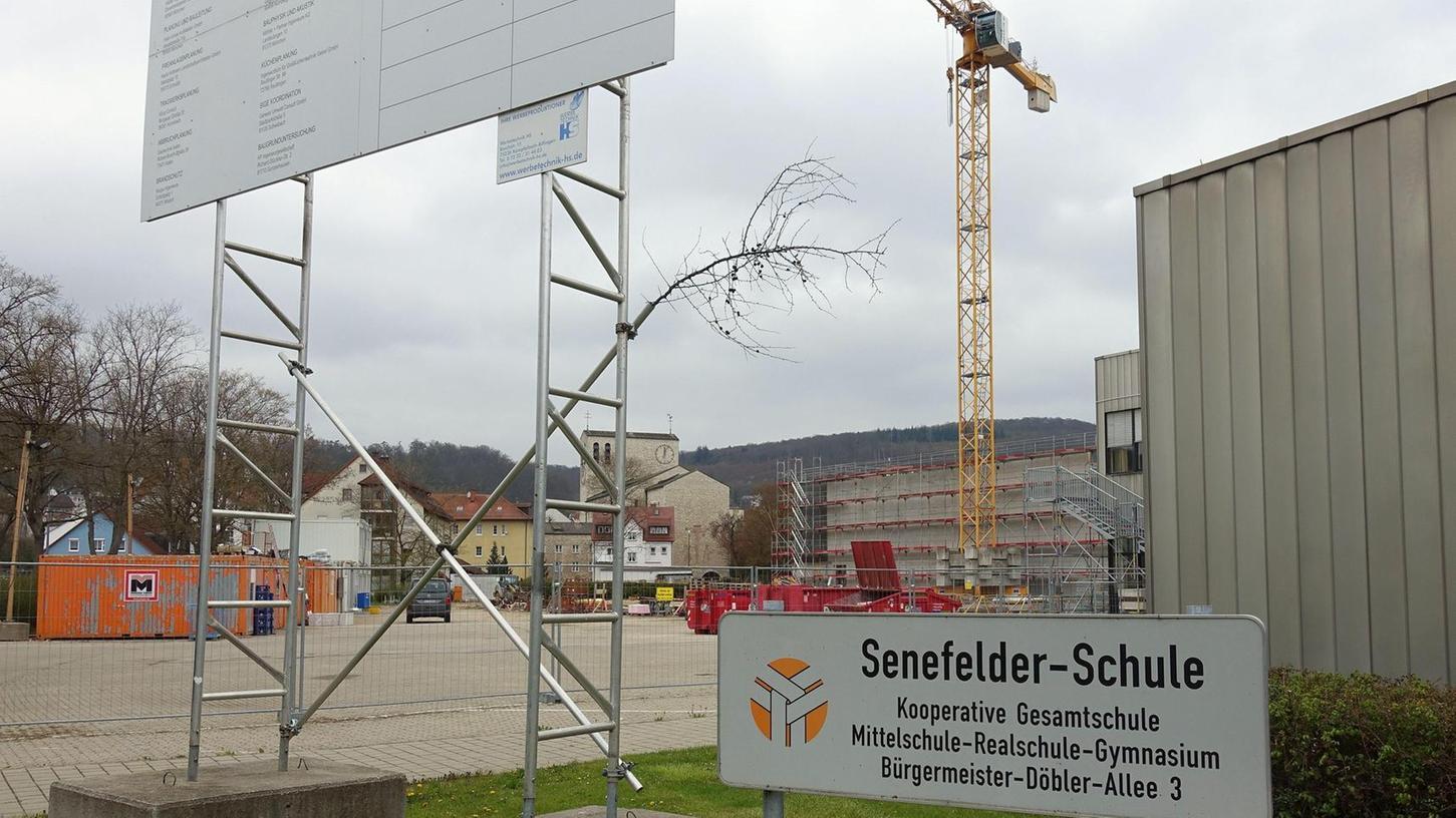Baustelle Senefelder-Schule: Zwischen der Ecke des Schulgebäudes und den Stützen für die Bautafel öffnet sich der Blick auf die Vierfach-Sporthalle nebst Mehrzweckhalle. Fassaden- und Dacharbeiten hierfür wurden nun vergeben.