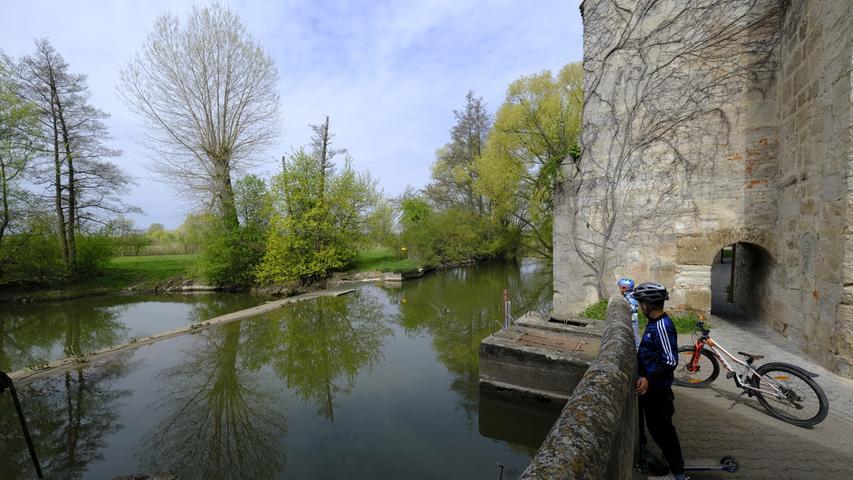 Die Aisch am Mühlenwehr, rechts die Schlossmauer.