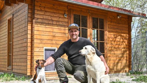 """Ralf Somann mit zwei seiner Hunde """"Lotti"""" und Georgi"""" vor einer seiner 15 Holzhütten für vierbeinige """"Hotelgäste"""" in seiner Hundeschule und Tierpension """"Somann´s"""" in Ruppmannsburg."""