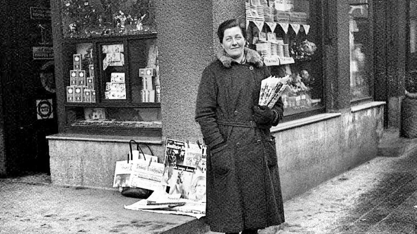 Scheinbar unverdrossen trotz winterlicher Temperaturen: Die unbekannte Straßenverkäuferin hat sich mit ihren Zeitungen und Zeitschriften vor einem Geschäft postiert. Wo und wann könnte dieses Bild entstanden sein?