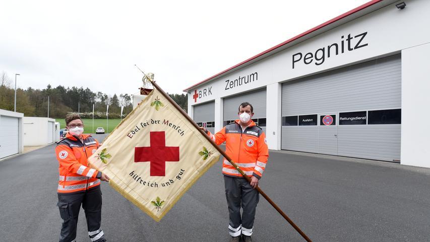 Bereitschaftsleiter Tobias Seeser und seine Stellvertreterin Sabrina Ziegler präsentieren stolz ihre Fahne vor dem neuen Dienstgebäude.