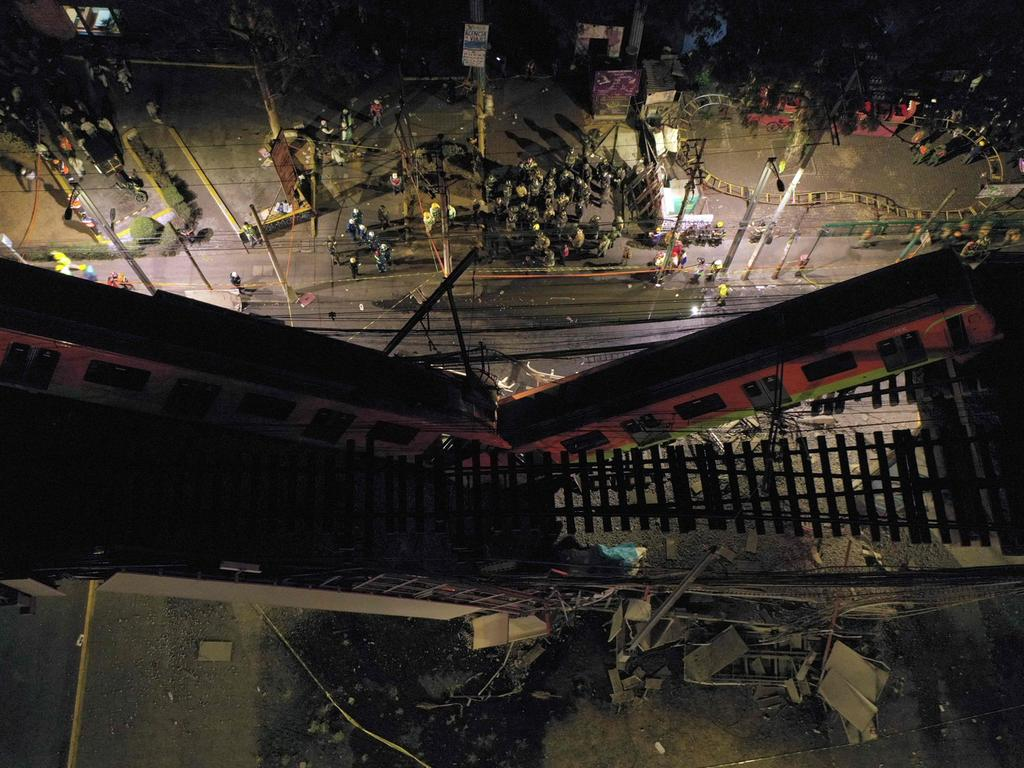 TOPSHOT - An aerial view shows rescue workers at the site of a metro train accident after an overpass for a metro partially collapsed in Mexico City on May 3, 2021. - At least 15 people were killed and dozens injured when an elevated metro line collapsed in the Mexican capital on May 3 as a train was passing, authorities said. (Photo by PEDRO PARDO / AFP)