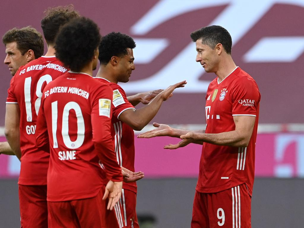 Bayern Munich's Polish forward Robert Lewandowski (R) celebrates scoring the 5-0 goal from the penalty spot with his team-mates during the German first division Bundesliga football match FC Bayern Munich v Borussia Moenchengladbach in Munich, southern Germany on May 8, 2021. (Photo by CHRISTOF STACHE / POOL / AFP) / DFL REGULATIONS PROHIBIT ANY USE OF PHOTOGRAPHS AS IMAGE SEQUENCES AND/OR QUASI-VIDEO