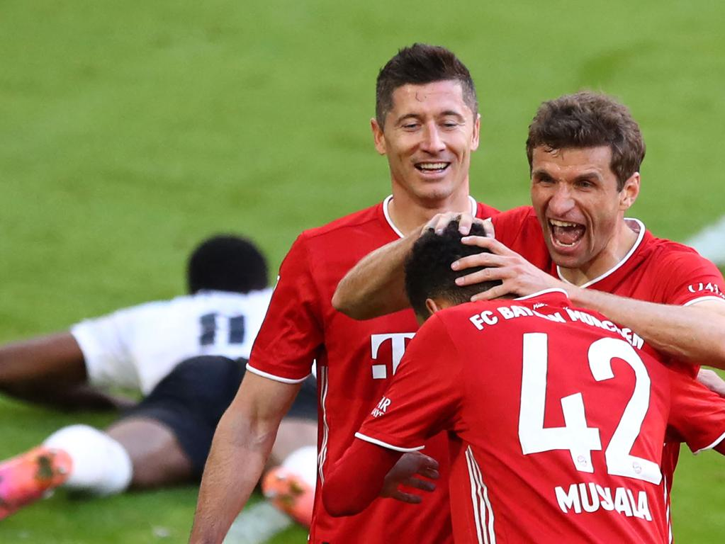 TOPSHOT - Bayern Munich's German forward Thomas Mueller (R) celebrates with Bayern Munich's Polish forward Robert Lewandowski (3rd R) and Bayern Munich's German midfielder Jamal Musiala (2nd R) after scoring the 2-0 during the German first division Bundesliga football match FC Bayern Munich v Borussia Moenchengladbach in Munich, southern Germany on May 8, 2021. (Photo by MATTHIAS SCHRADER / POOL / AFP) / DFL REGULATIONS PROHIBIT ANY USE OF PHOTOGRAPHS AS IMAGE SEQUENCES AND/OR QUASI-VIDEO   ALTERNATIVE CROP