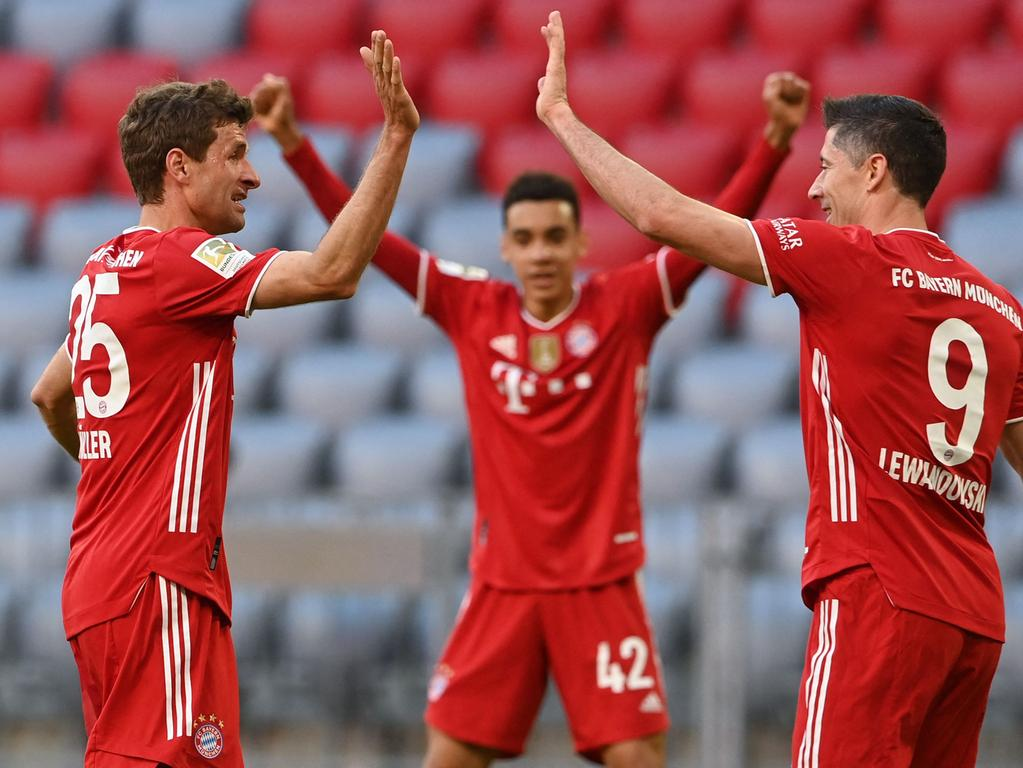 Bayern Munich's German forward Thomas Mueller (L) celebrates scoring the 2-0 goal with his team-mates Bayern Munich's Polish forward Robert Lewandowski (R) and Bayern Munich's German midfielder Jamal Musiala (C) during the German first division Bundesliga football match FC Bayern Munich v Borussia Moenchengladbach in Munich, southern Germany on May 8, 2021. (Photo by CHRISTOF STACHE / POOL / AFP) / DFL REGULATIONS PROHIBIT ANY USE OF PHOTOGRAPHS AS IMAGE SEQUENCES AND/OR QUASI-VIDEO