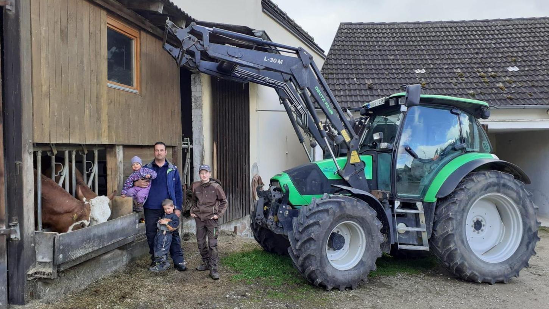 Thomas Schütz mit seinen Kindern Elena, Leon und Jonathan (v.li.) beim Füttern der 50 Kühe des Bauernhofs.