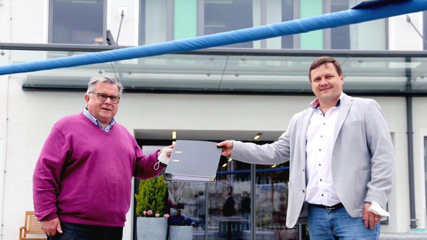 Gerhard John überreicht dem Altdorfer Rathaus-Chef Martin Tabor die Bauakte.