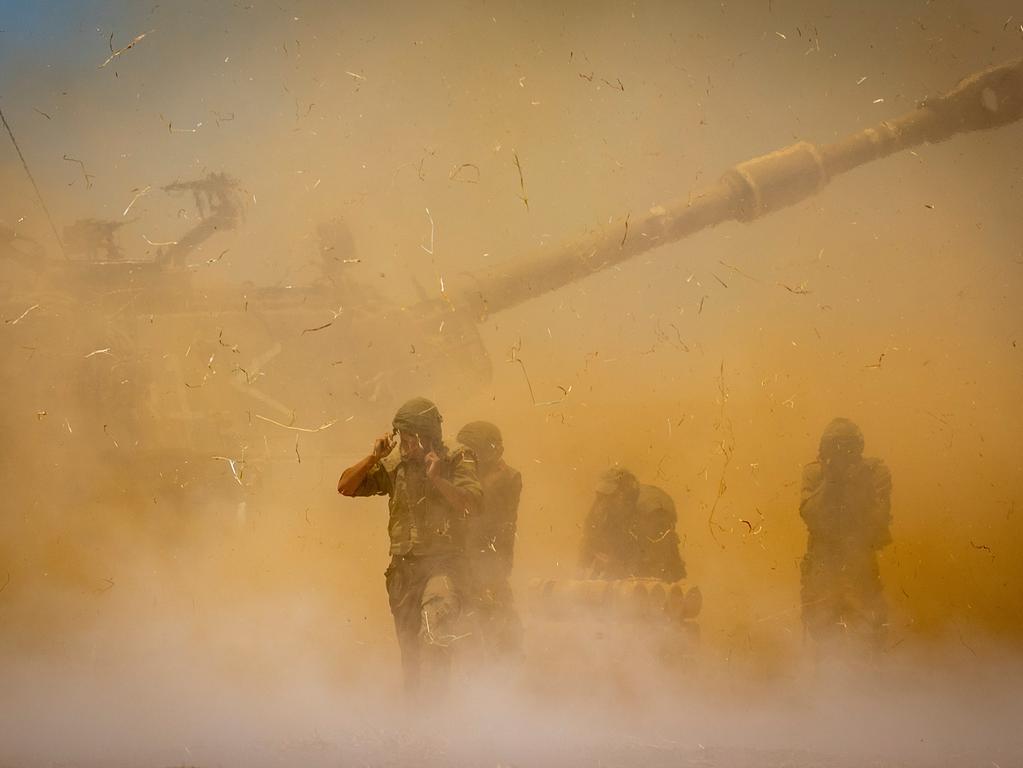 12.04.2021, Israel, ---: Israelische Soldaten stehen in aufgewirbeltem Staub, nachdem ein Artilleriegeschütz auf Ziele im Gazastreifen gefeuert hat. Seit dem 10. Mai beschießen militante Palästinenser Israel mit Raketen. Israels Armee reagiert darauf mit Angriffen auf Ziele im Gazastreifen, vor allem durch die Luftwaffe. Auf beiden Seiten gab es Tote. Foto: Yonatan Sindel/AP/dpa +++ dpa-Bildfunk +++