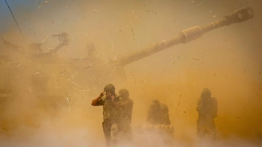Israelische Soldaten stehen in aufgewirbeltem Staub, nachdem ein Artilleriegeschütz auf Ziele im Gazastreifen gefeuert hat.
