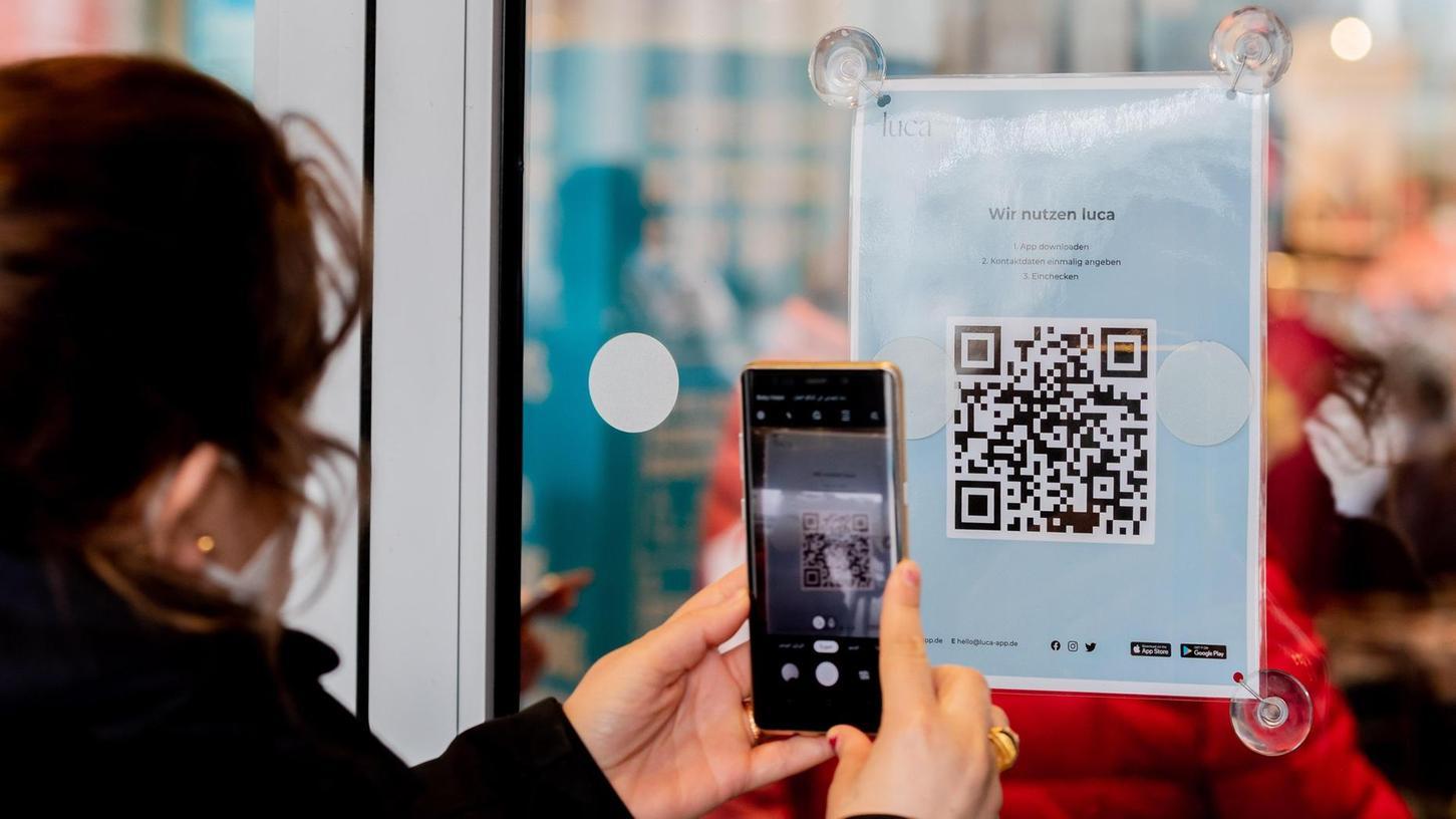 Daten sammeln für eine mögliche Kontaktnachverfolgung: Eine Frau scannt am Eingang eines Berliner Geschäfts einen QR-Code zum Download der Luca-App.