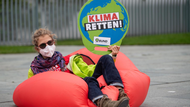 Eine Umweltaktivistin hält bei einer Demonstration für mehr Klimaschutz vor dem Bundeskanzleramt ein Plakat mit der Aufschrift