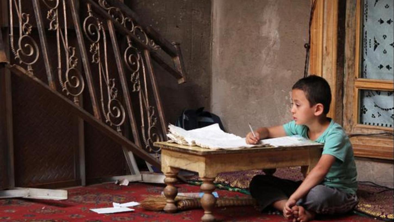 Keine Idylle, aber auch keine Elends-Fotografie: Die Bilder, die Laurence Grangien aus der chinesischen Provinz Xinjiang mitgebracht hat, zeigen die Uiguren in ihrem Alltag – wie dieses zwischen schmuckvoller Möblierung und Verfall lernende Kind.
