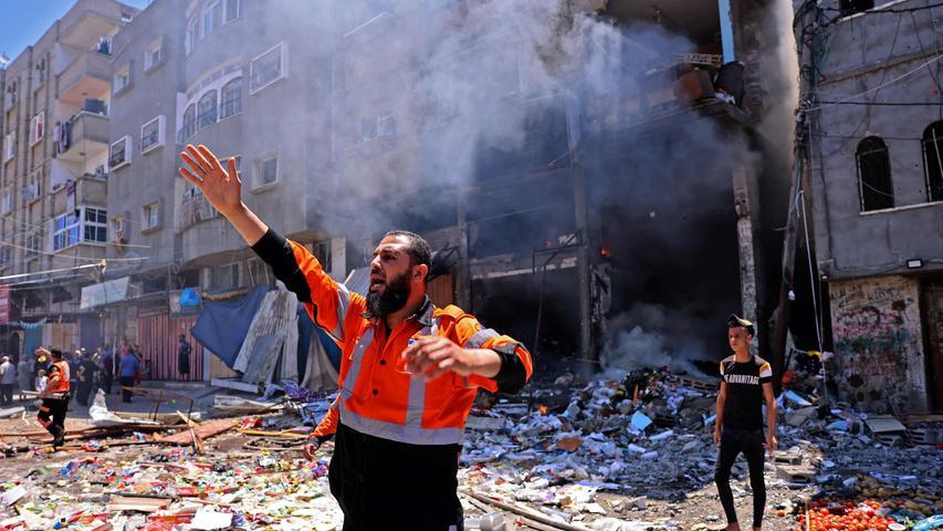 Ein palästinensischer Feuerwehrmann dirigiert seine Kollegen nach einem israelischen Raketenangriff im Gaza-Streifen. Viele Menschen starben dort, nachdem die Gewalt eskalierte. Mehr dazu lesen Sie hier.